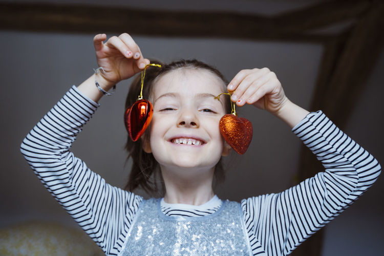 Portrait of smiling girl holding heart shaped decorations
