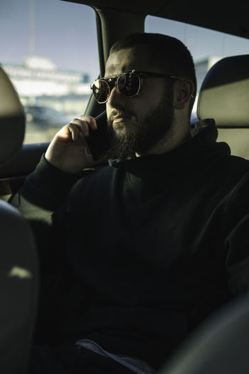 Man talking on mobile phone while traveling in car