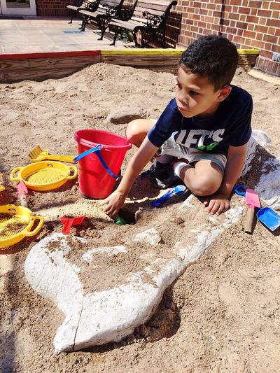 High angle view of boy playing with toys in sandbox on sunny day
