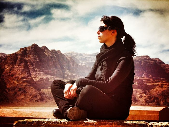 Woman sitting on rock formation against sky at wadi rum