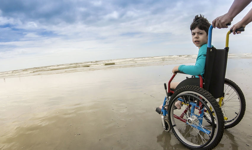 Cropped parent pushing son in wheelchair at beach
