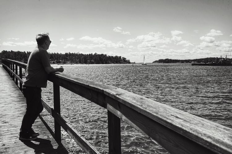 Man standing on railing by lake against sky