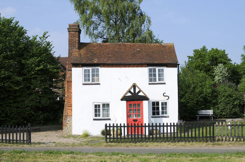 White painted country cottage house with red door Architecture Building Exterior Built Structure Cottage, Country Property Façade Home House Outdoors Residential Structure Rural Scene White