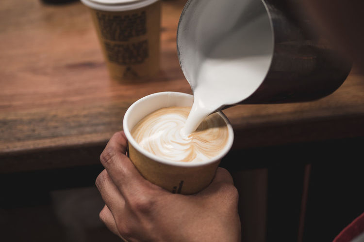 Cropped Image Of Hand Pouring Milk In Coffee