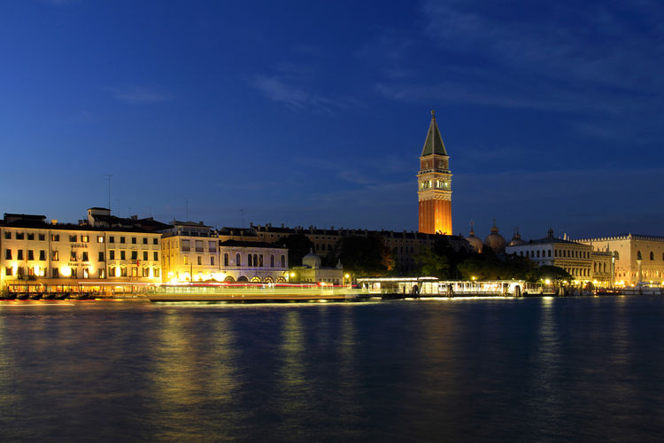 San marco campanile tower in illuminated city by canal at night
