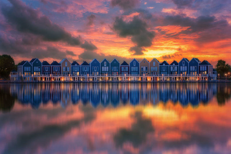 """Dutch architecture in Houten, Holland. The houses are also called """"The Rainbow Houses"""" because of their vibrant colors Amsterdam Colors EyeEm EyeEm Best Shots EyeEm Gallery EyeEmBestPics EyeEmNewHere Holiday Home Houses Netherlands Reflection Sunset_collection Tadaa Community Travel Architecture Clouds And Sky Dutch Landscape Evening Sky Eye4photography  Fall Holland Reflections In The Water Sky Sunset"""
