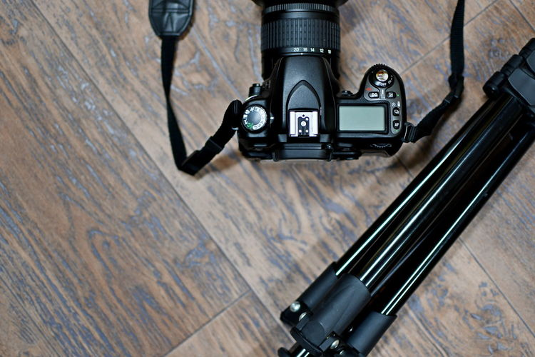 Directly above shot of dslr camera with tripod on wooden table