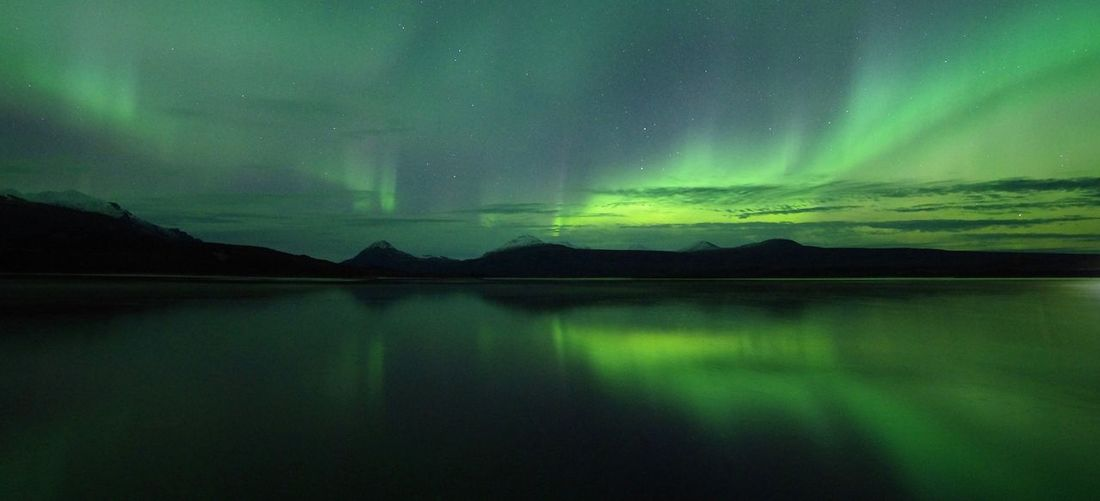 Scenic view of lake with aurora borealis against sky at night