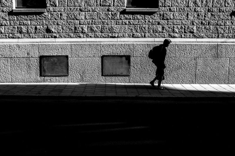 Full length of silhouette man walking against wall