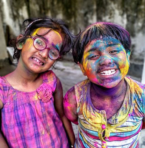 Portrait Of Smiling Sisters With Powder Paint On Face During Holi
