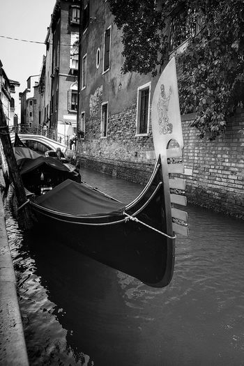 Boats moored in canal by city