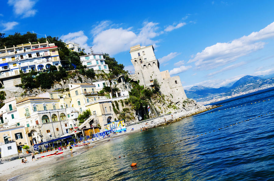 Cetara, Italy - October 2, 2013: Cetara small beach village on the Amalfi Coast, LA beach is defended by an ancient Saracen tower. Bathers on the beach on a warm October day. In the background you can see the city of Salerno Architecture Blue Building Exterior Built Structure City City Life Cloud Cloud - Sky Day Mountain Nature Outdoors Residential Building Residential District Residential Structure Scenics Sky Tourism Tourist Town TOWNSCAPE Travel Destinations Vacations Water