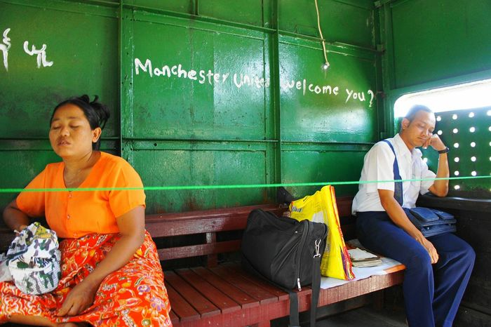 "My Commute ""Manchester United Welcome You?"" The ""VIP"" section at the back of the Circle Train in Yangon is marked by a Green rope. A man and a woman rests as the train travels out of the city. On the wall behind them someone has written a greeting to Manchester United (?). Yangon Rangoon Myanmar Burma Train Circle Train Manchester Manchesterunited Manchester United Question Mark Sleeping Trainphotography Travelphotography Worldcaptures Eyeem Myanmar EyeEm Best Shots EyeEm Masterclass Vip Grafitti Tagging Commuting Newstrekker Travel Photography Wanderlust"