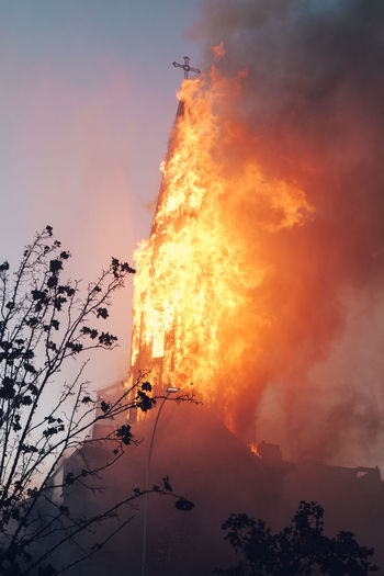 Low angle view of fire against sky at sunset