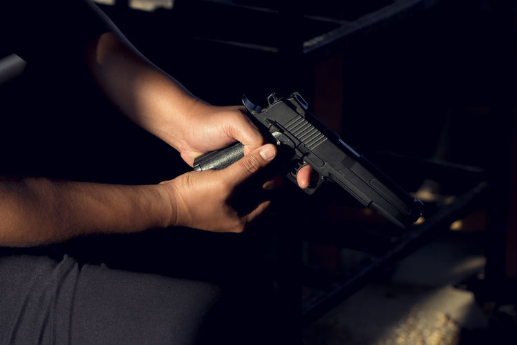 Midsection of man holding handgun while sitting on chair in room