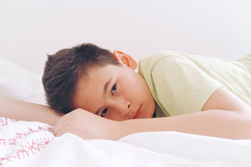 Portrait of cute boy resting on bed at home