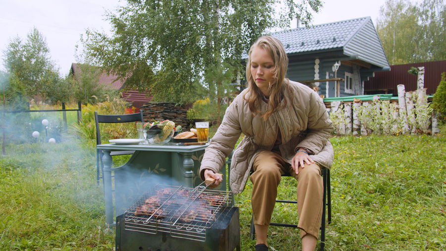 Young man sitting on barbecue grill in yard