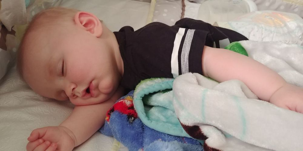 Close-up of cute baby boy sleeping on bed at home