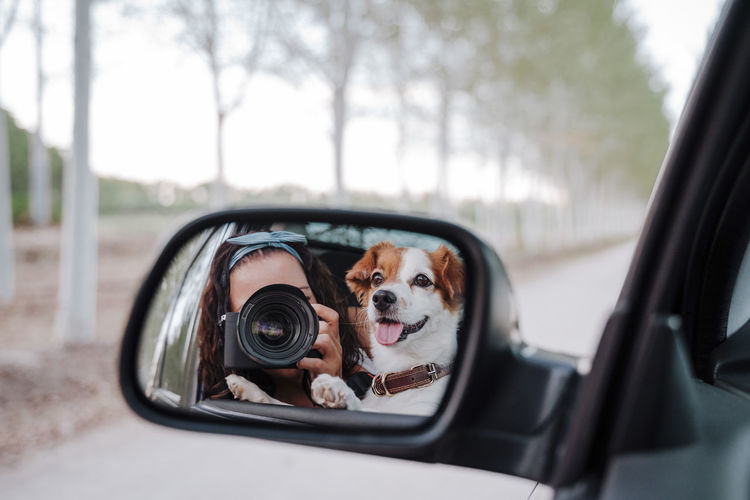 Woman photographing with dog reflecting in car