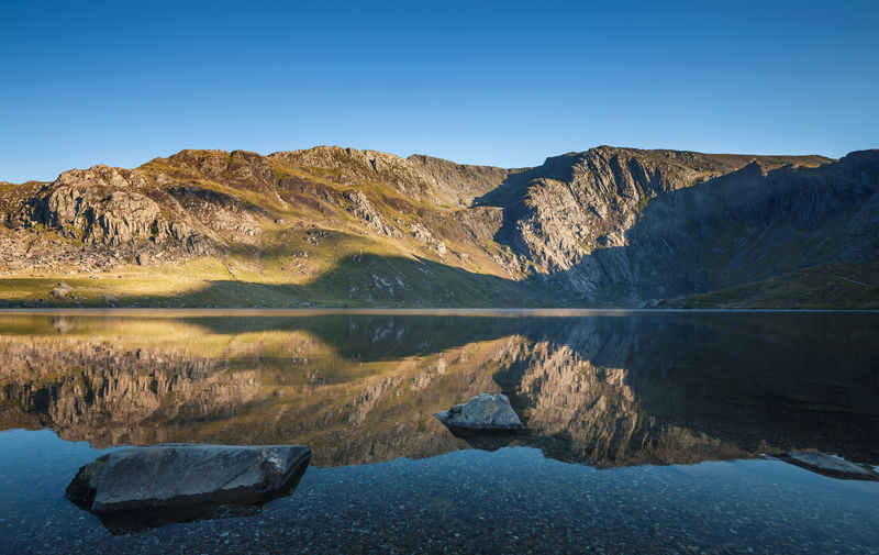 Cwm Idwal Lake in Snowdonia, North Wales Clear Blue Sky Ice Age Beauty In Nature Blue Calm Water Clear Water Crystal Clear Day Lake Lake View Landscape Mountain Mountain Lake Mountain Range Nature No People Outdoors Reflection Rock - Object Rocky Mountains Scenics Sky Tranquil Scene Tranquility Water