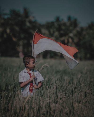 Boy holding umbrella on field