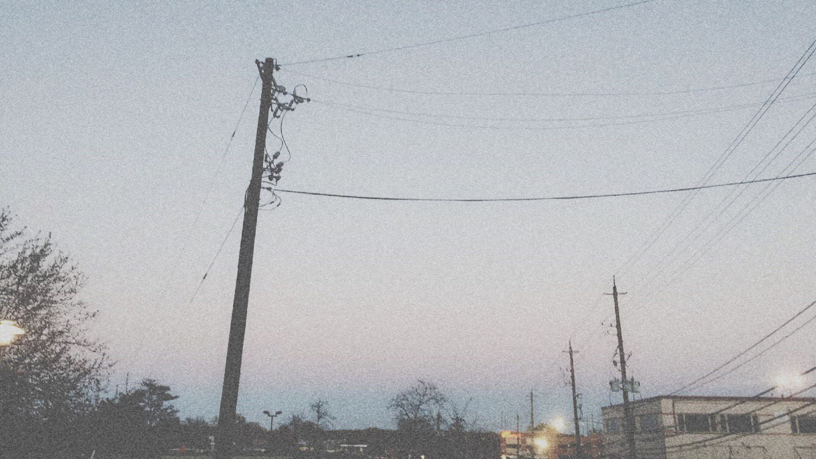power line, building exterior, architecture, built structure, electricity pylon, cable, low angle view, electricity, clear sky, power supply, fuel and power generation, connection, sky, technology, outdoors, street light, power cable, house, day, residential structure