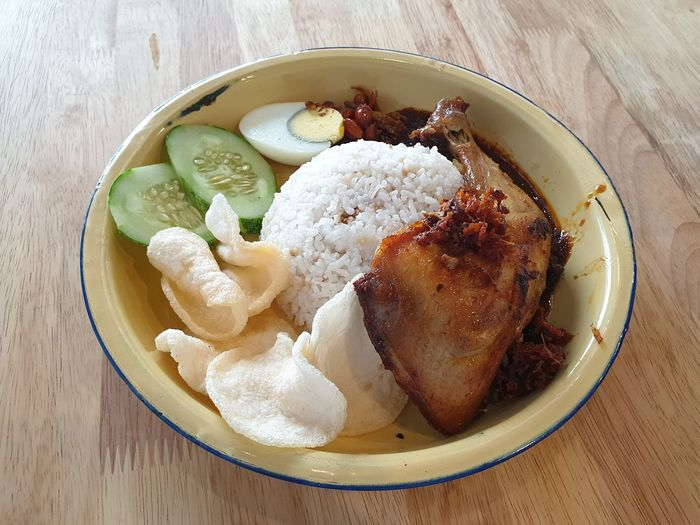 Nasi lemak is a Malay fragrant rice dish cooked in coconut milk and pandan leaf. It is commonly found in Malaysia, where it is considered the national dish; it is also popular in neighbouring areas such as Singapore; Brunei, and Southern Thailand. Coconut Milk Fragrant Rice Local National Food Nasi Lemak Breakfast Lunch Time Lunch Dinner Pandan Leaves EyeEm Selects Table High Angle View Close-up Food And Drink Served
