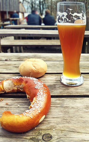 Relax at beer garden, Bavarian beer and pretzel. More than food, beer and pretzel are the symbol of Bavarian way of life, a moment shared with friends in a beer garden or at Oktoberfest Bavaria Beer Drinking Beer Garden Beer Glass Biergarten Bread Close-up Day Drink Drinking Glass Food And Drink Freshness Healthy Eating Leisure Time Lifestyles Munich, Germany No People Outdoors Pretzel Refreshment Table Wooden Bench
