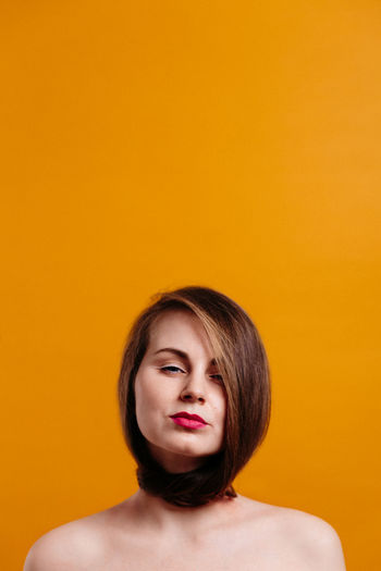 Portrait of beautiful woman against yellow background