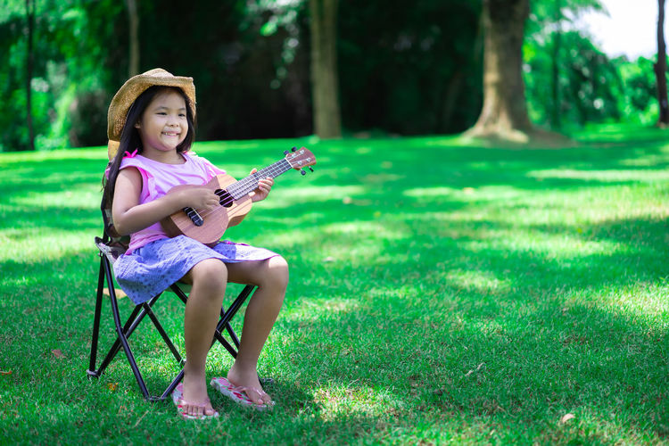 Full length of smiling girl playing guitar sitting on chair at park