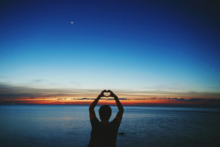 Silhouette man making heart shape while standing at beach against blue sky during sunset