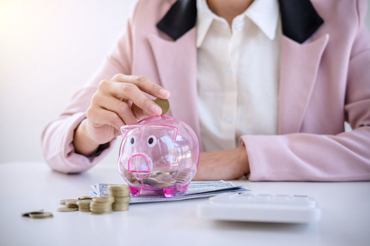 Midsection of businesswoman putting coin in piggybank