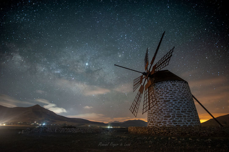 Windmill against sky at night