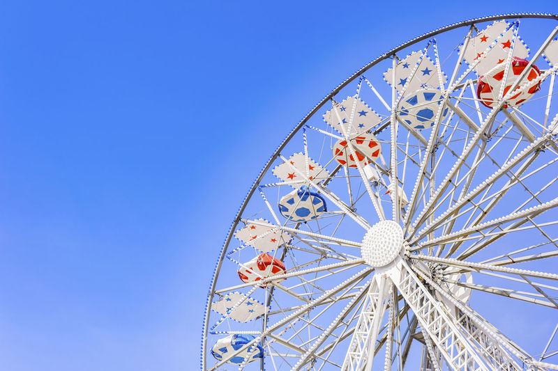 High section of ferris wheel against clear blue sky