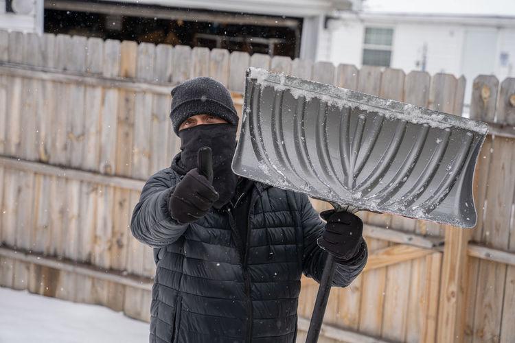 Man holding umbrella standing in snow