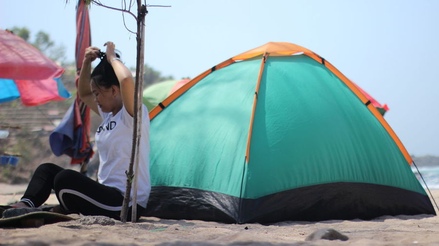 Side view of woman sitting by tent on beach against clear sky