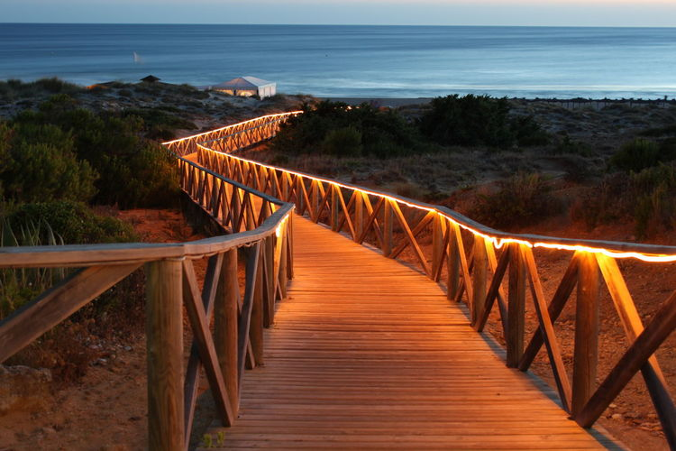 Empty Illuminated Boardwalk Leading Towards Beach At Dusk