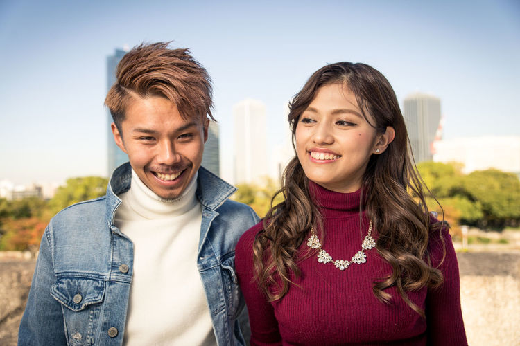 Portrait of smiling young couple standing against sky