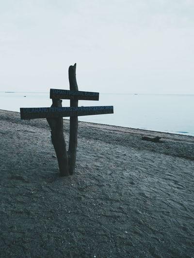Cross on shore against sea against sky