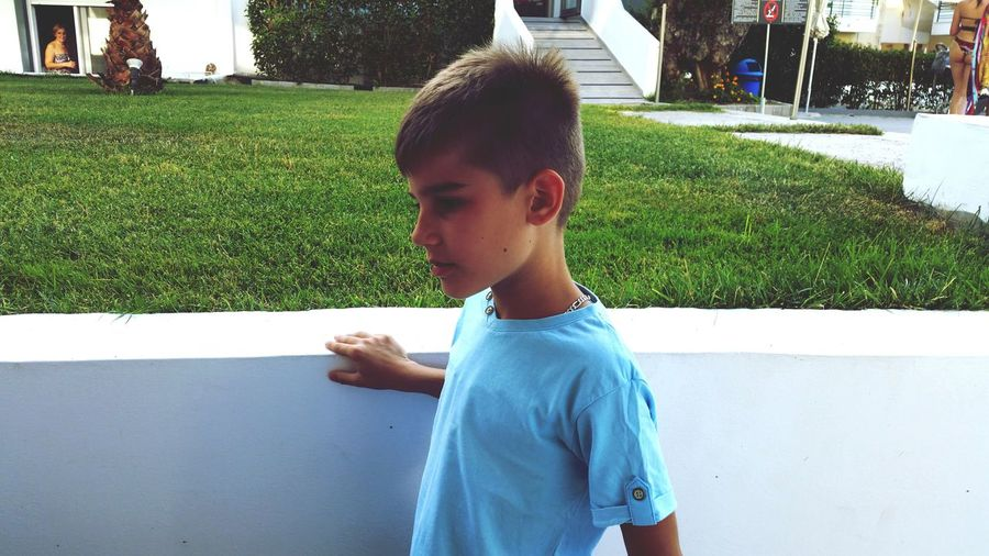 Side view of boy looking away while standing by retaining wall in city