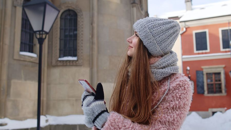 Woman wearing hat against building during winter