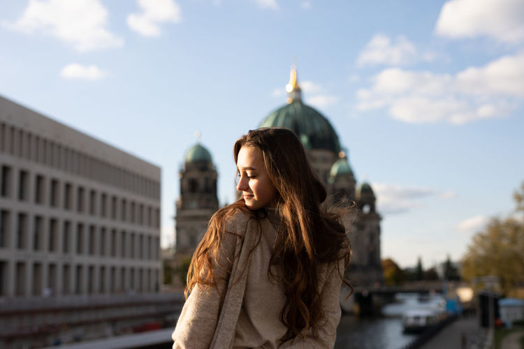 Young woman with eyes closed standing in city against sky