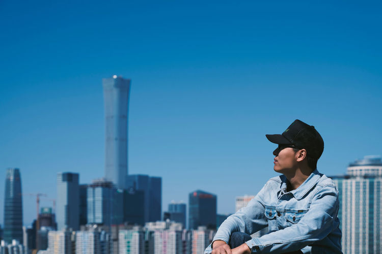 Man looking away with buildings in background against clear blue sky