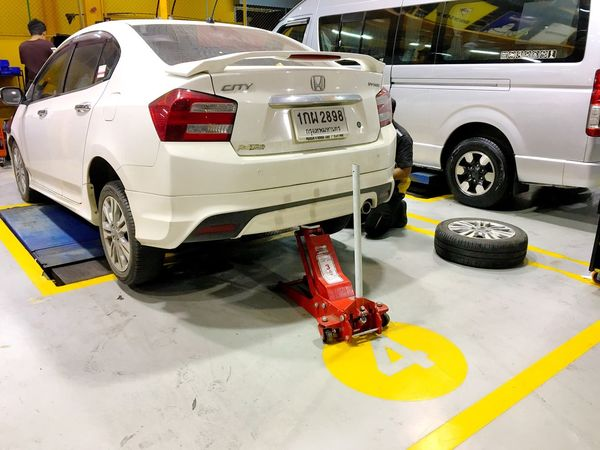 A white Honda City car was lifted by a red hydraulic jack in the garage. Hua Hin, Thailand September 1,2017 Wheel Shock Absorber Change Engine Oil Check Car Bumper Garage Mechanic Fix  Inflat Broken Spoiler Honda Rear Lights Hydraulic Jack Hydraulic System Hydraulic Care Car Transportation Mode Of Transportation Motor Vehicle Car Land Vehicle Road Street Day City White Color Travel