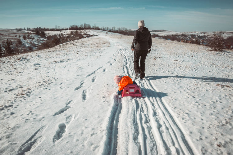 Rear view of parent pulling sled with child on snow covered field