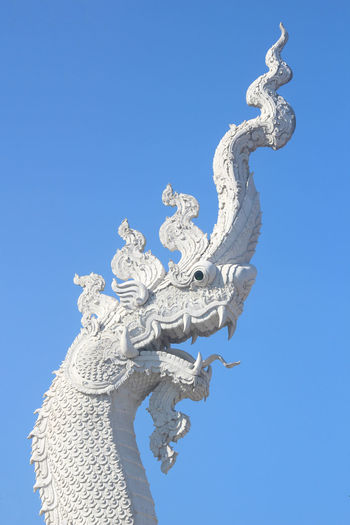Low Angle View Of Dragon Statue Against Clear Blue Sky