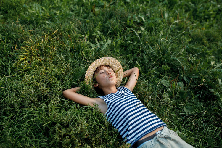 Teenage boy making face while lying on grass outdoors