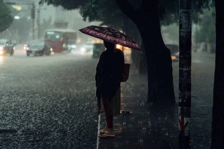 Rear view of person walking on wet street during rainy season