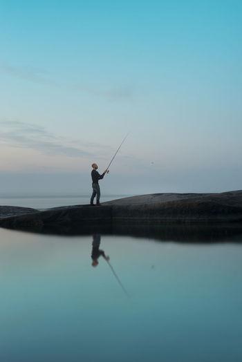 Silhouette man fishing in lake against sky