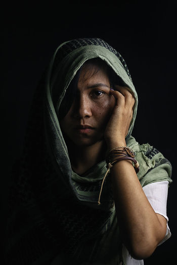 Portrait of young woman covered with scarf against black background